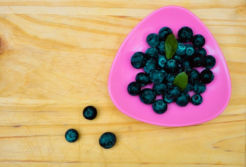 top view of blueberries on wood background
