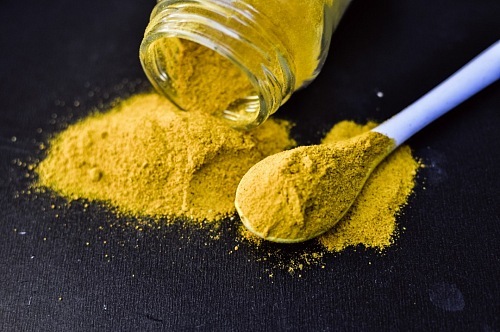 heap of yellow curcuma turmeric spices powder isolated on Black background