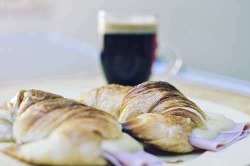 Fresh croissants with ham and cheese on plate and coffee cup